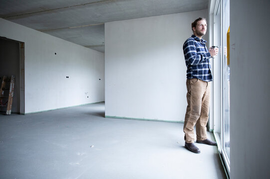 Construction worker looking through window while standing in renovating house