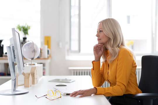 Businesswoman using computer on desk while sitting in home office