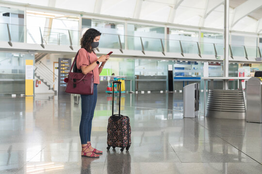 Young woman with protective face mask text messaging on smart phone while standing at airport