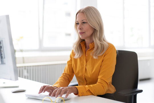 Confident businesswoman using computer on desk in home office