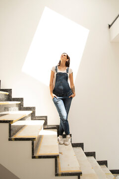 Pregnant woman with hands in pockets standing on steps against wall in new house