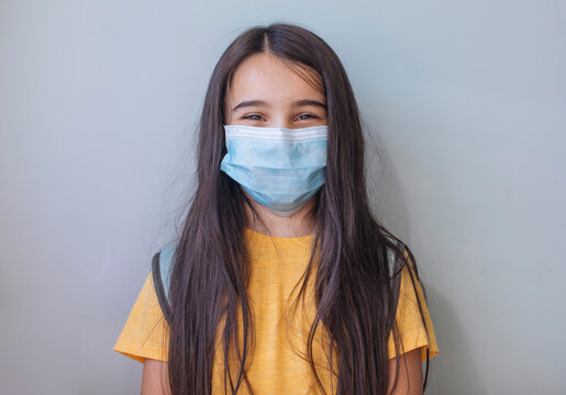School girl with face mask standing against gray wall
