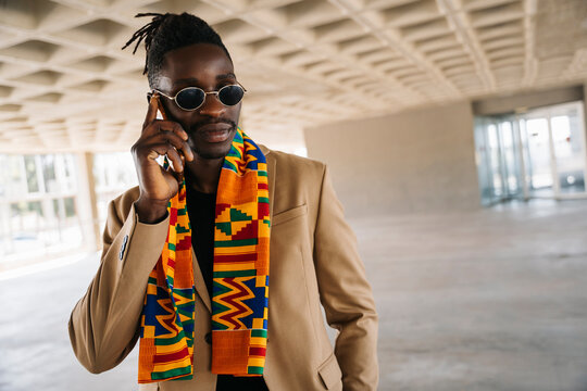 Fashionable man wearing traditional kenete talking on phone while standing in building