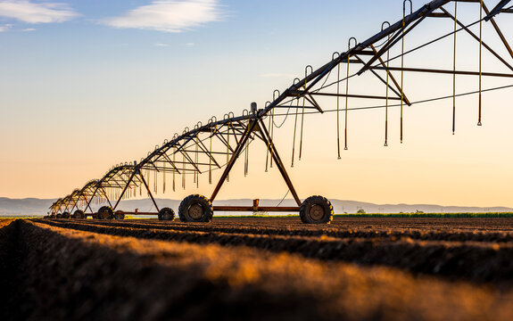 Irrigation equipment on field against sky during sunset