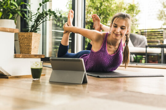 Young woman looking in digital tablet while practicing yoga on mat at home