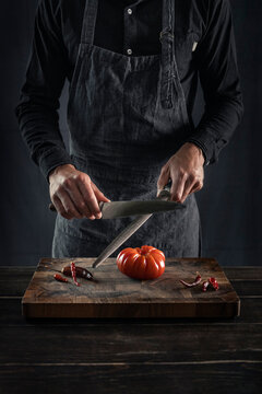 Man sharping knife while standing at table