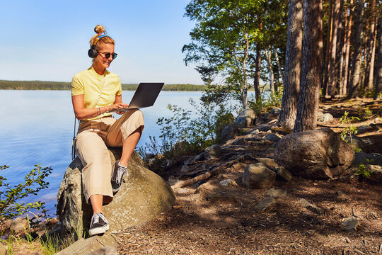 Mid adult woman wearing sunglasses using laptop while sitting against lake in Tiveden National Park, Sweden