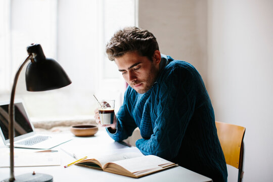 Male architect holding coffee reading book while sitting at desk in office