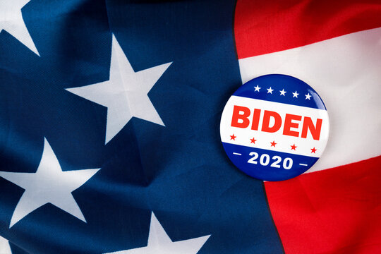 biden presidential election campaign 2020 vote button; pin laying on the american flag. Voting; ballot and politics concept.