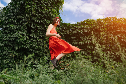beautiful young rebel brunet girl in red dress in green park bushes walking in black shoes. Color contrast expressive fashion style move. Conceptual artistic horizontal composition Stylish brutal teen