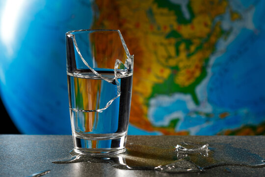 broken glass and its fragments with leaked water on the background of the globe, map of america