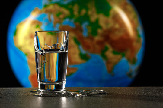 broken glass from which water flows, in the background the planet earth africa and eurasia