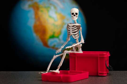 the skeleton sits on a red plastic box that is open, background planet earth map of north america