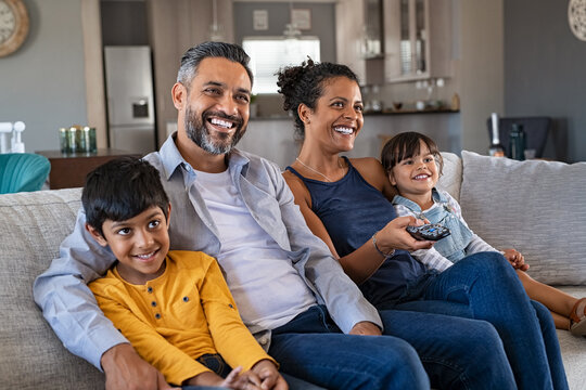 Happy ethnic family watching television together