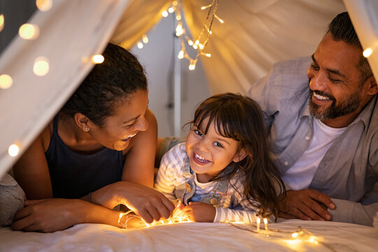 Happy ethnic family playing together in cozy hut with daughter