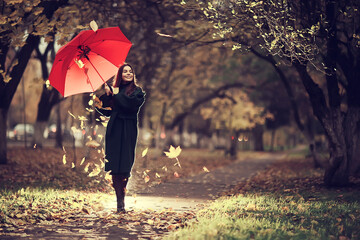 girl with umbrella posing in autumn park, october landscape lonely woman holding a red umbrella