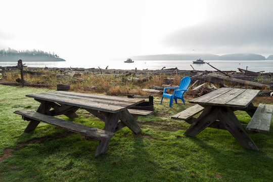Picnic tables and blue chair at Spencer Spit State Park on Lopez Island, Washington, USA