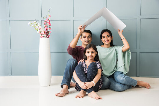 Real Estate Concept - Indian happy and young family of Four holding house roof made of cardboard