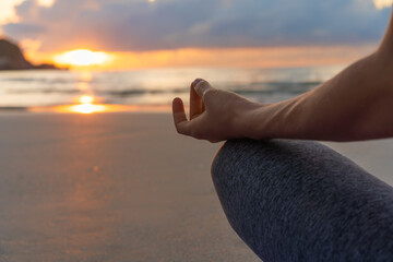 Woman sitting in lotus position and meditating at sunrise on the beach