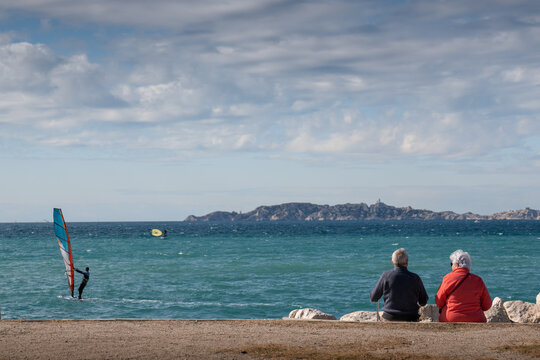 A retired couple in love sitting on a bench look at the sea - lovers concept