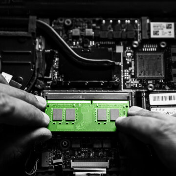 Close-up on the green RAM memory that the hands of the service technician insert into the slot on the laptop computer.