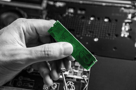 The service technician holds a new green ssd drive in his hands, which he wants to put in the laptop, and he hopes that after that it will work. Black and White.