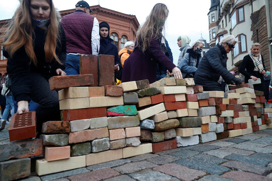 """People lay bricks in the Doma square during  """"Wall of Misunderstanding"""" protest action in Riga"""