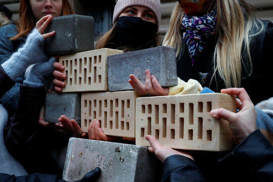 "People hold bricks next to the Parliament House during  ""Wall of Misunderstanding"" protest action in Riga"