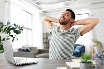 technology, remote job and business concept - happy smiling man with laptop computer stretching at...