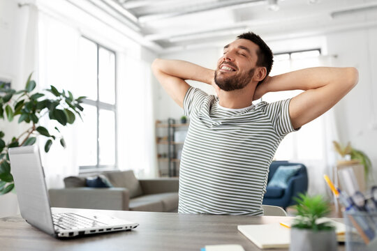 technology, remote job and business concept - happy smiling man with laptop computer stretching at home office
