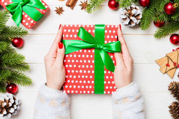 Wall Mural - Top view of a woman holding a gift box in her hands on festive wooden background. Fir tree and Christmas decorations. New year time concept