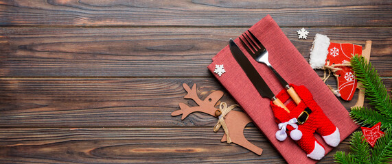 Wall Mural - Banner top view of holiday objects on wooden background. Utensils tied up with ribbon on napkin. Christmas decorations and reindeer with copy space. New year dinner concept