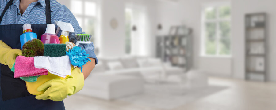 Maid standing inside home holding a bucket fulfilled with chemicals and facilities for tidying - Web banner
