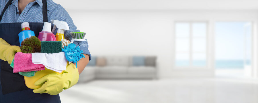 A cleaning woman is standing inside a building holding a bucket fulfilled with chemicals and facilities for tidying -Web banner