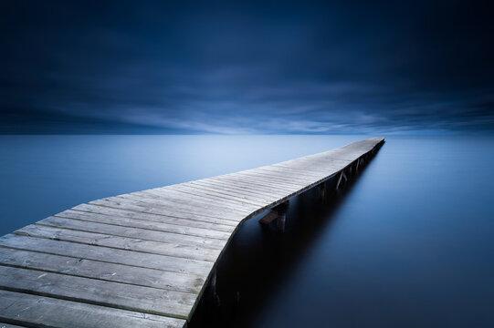 Dark blue atmosphere around a pier to the lake of Sanguinet
