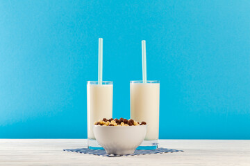 Breakfast cereal balls and milk in glass against blue background