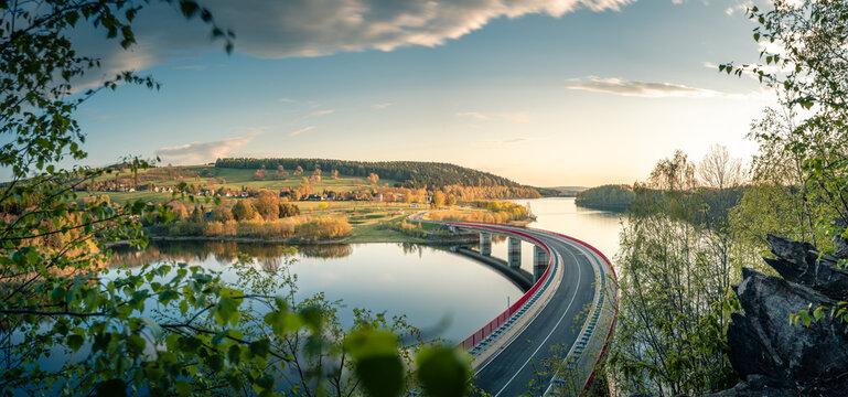 Landstraße mit Brücke über Stausee
