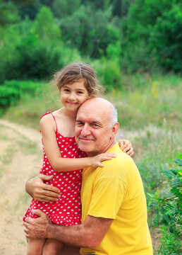 Portrait of Happy granddad and grandaughter playing at the park