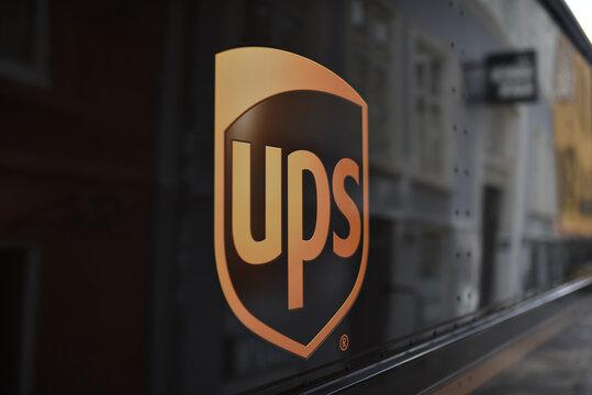 Copenhagen / Denmark - 07.23.19: Logotype of UPS (United Parcel Service) on body truck with street reflection