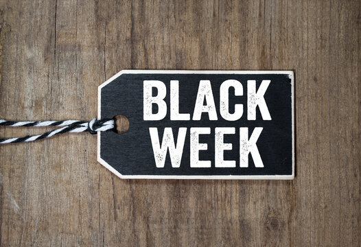 Black wooden hang tag with message Black Week on weathered wood background