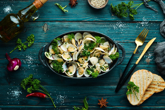 Boiled shellfish in shells with garlic and parsley in a black plate. Seafood. Top view. Free space for text.