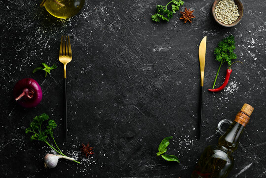 Kitchen banner: Spices, vegetables and cutlery on a black stone background. Top view. Free space for text.