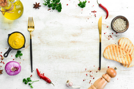 Kitchen banner: Spices, vegetables and cutlery on a white wooden background. Top view. Free space for text.