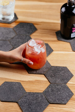 red alcoholic cocktail in hand on wooden background
