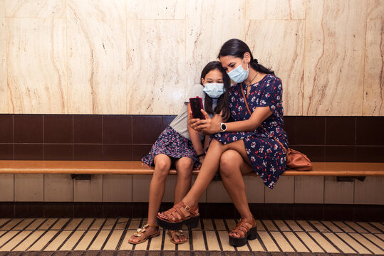 Little girl and her young mother taking a selfie wearing surgical mask. Girls sitting on the bench at the train station.