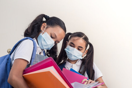 Two little girls studying wearing face mask during covid contagion. Notebooks in hands stands