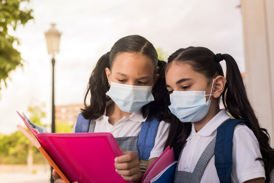 Schoolgirls wear face mask and read the notebook in their hands at outdoor.