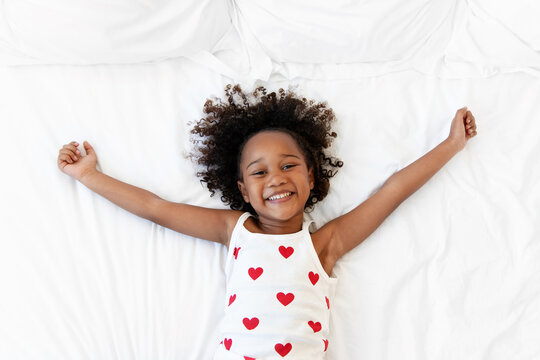 Happy little girl lying on bed with arms extended