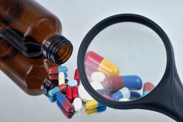 Examiner un mélange de médicaments sortis d'un flacon avec une loupe en gros plan Wall mural