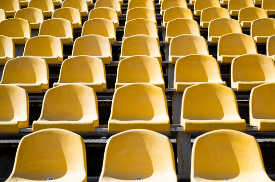 empty yellow seats on outdoor sport stadium arena for football fans, big game
